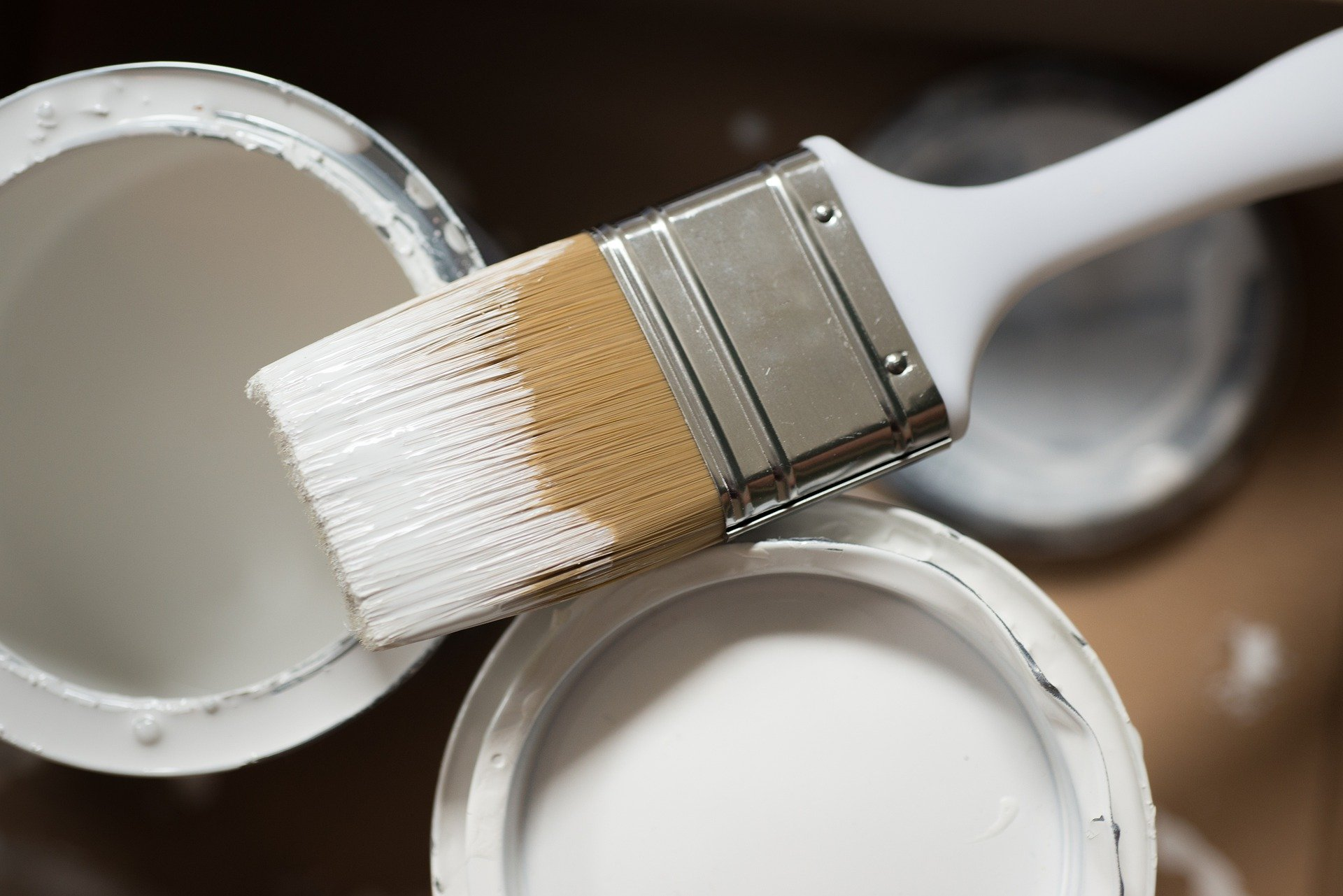 Paint brush resting on tin of white paint